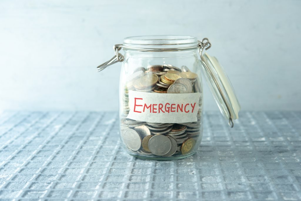 Coins in glass money jar with emergency label, financial concept.